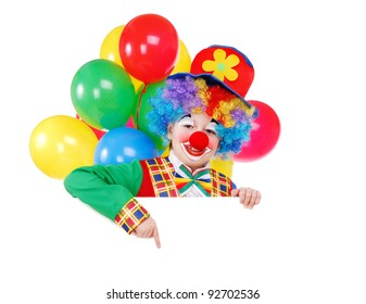 Birthday clown with balloons pointing with his finger to the blank board over the white background