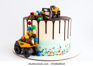 Birthday colorful cake for little boy with toy cars and colorful candies decorations. Holiday, celebration, stylish concept. Construction and transportation theme boys party.