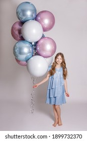 birthday concept - full length portrait of happy beautiful girl posing with pastel air balloons over white background