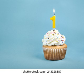 A birthday cup cake with buttercream icing,  sprinkles and a lit number one birthday candle.