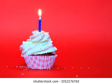 Birthday cup cake with candle, whipped cream and sugar balls on red background. Happy birthday, one year birthday celebration