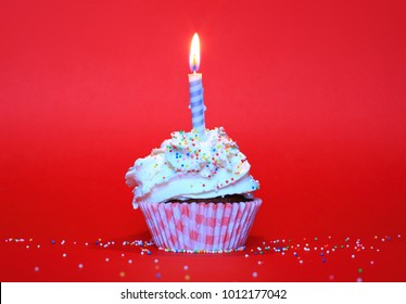 Birthday cup cake with candle, whipped cream and sugar balls on red background. Happy birthday, first birthday party