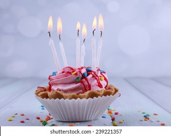 Birthday Cup Cake With Candles And Sparkles On Color Wooden Table Light Background