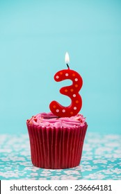 birthday cup cake with number three candle on blue background
