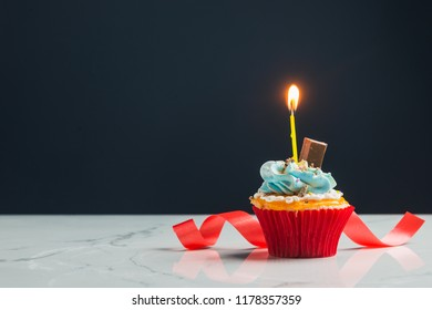 Birthday cupcake with buttercream icing and orange candle over a grey background. Gift for every one.