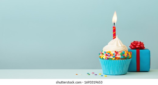 Birthday cupcake with candle and gift box