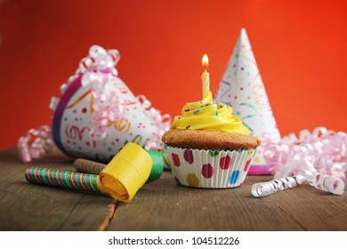 Birthday cupcake with candle and birthday hats in background