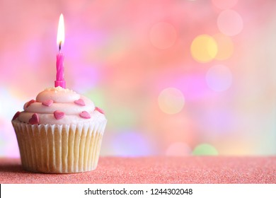 Birthday cupcake and candle on colorful defocused background party concept