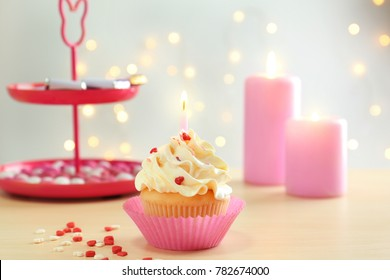 Birthday cupcake with candle on table against blurred background