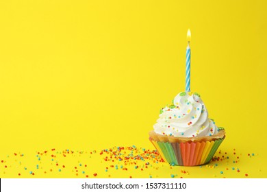 Birthday cupcake with candle on yellow background, space for text. Greeting card