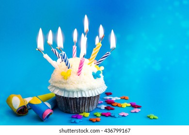 birthday cupcake with candles on blue background with colorful decoration