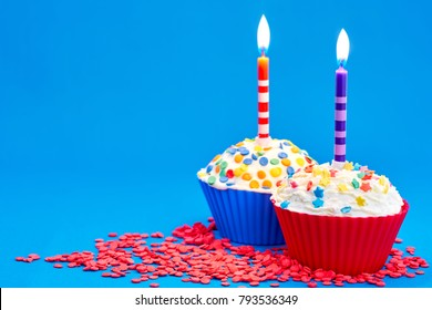 Birthday cupcake with a candles on blue background
