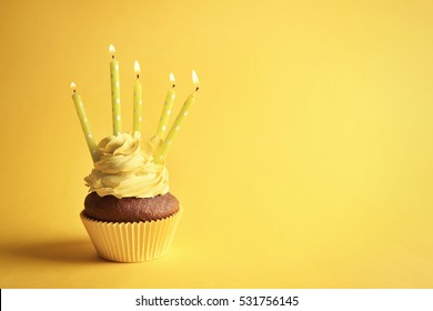 Birthday cupcake with candles on yellow background