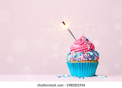 Birthday cupcake with celebration sparkler and colorful pink and blue sugar sprinkles