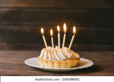 Birthday cupcake with five candles on a plate on wooden background.