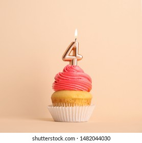 Birthday cupcake with number four candle on beige background