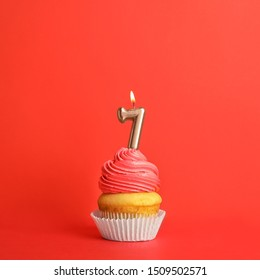 Birthday cupcake with number seven candle on red background