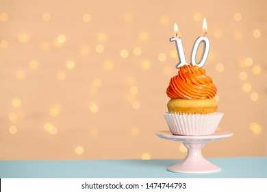 Birthday cupcake with number ten candle on stand against festive lights, space for text