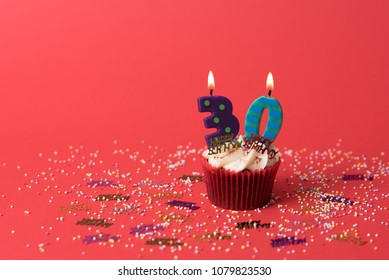 Birthday cupcake with number thirty candle on red background