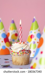 Birthday cupcake with one candle and party hats