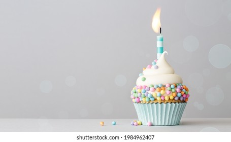 Birthday cupcake with pastel colored sprinkles and one birthday cake candle on a gray background with copyspace to side