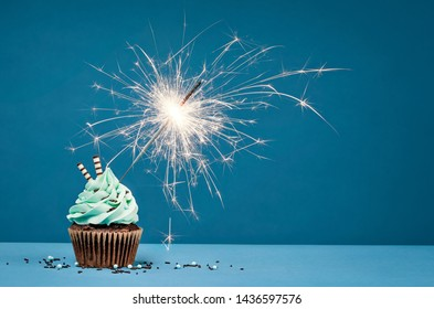 Birthday Cupcake with sparkler against a blue background.