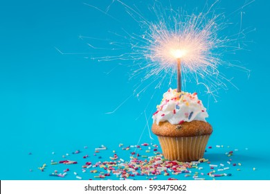 Birthday Cupcake with a sparkler on blue background