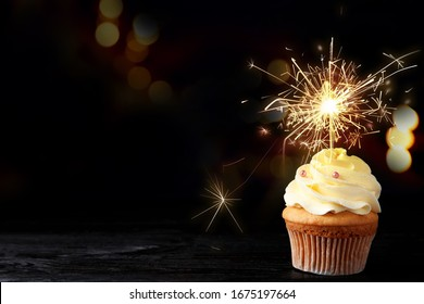 Birthday cupcake with sparkler on table against dark background. Space for text