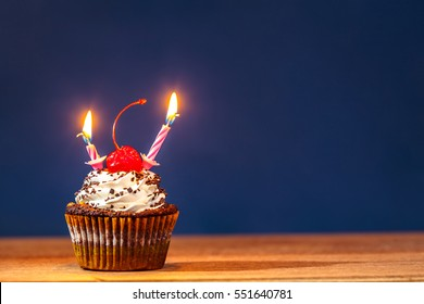 Birthday Cupcake With Two Burning Candles And A Red Cherry On Top Over Deep Blue Background
