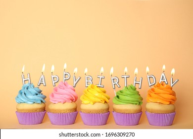 Birthday cupcakes with burning candles on beige background. Space for text