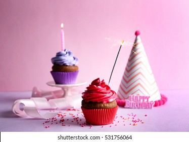 Birthday cupcakes with candle and sparkler on pink background