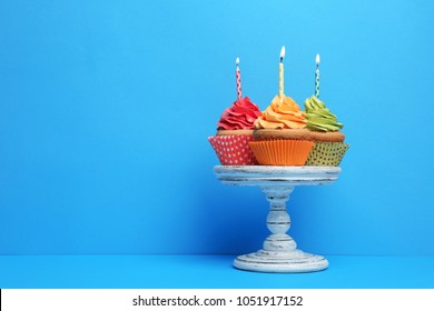 Birthday cupcakes with candles on stand against color background