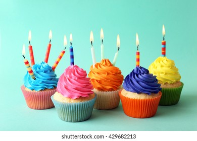 Birthday cupcakes with candles on turquoise background