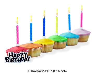 Birthday cupcakes in different colors isolated on white background