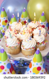 Birthday cupcakes with lit candles and party hats