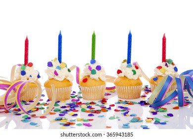 Birthday cupcakes in a row with colorful confetti over white background
