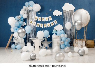 Birthday decorations - gifts, toys, balloons, garland and figure for little baby party on a blue wall background. - Shutterstock ID 1809968425