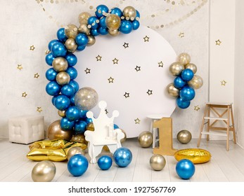 Birthday decorations - gifts, toys, balloons, garland and number for little baby party event on a white wall background.