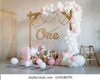 Birthday decorations with wooden arch, gifts, toys, balloons, garland and figure 1 for little baby party on a white wall background.