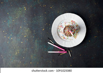 Birthday double chocolate cupcake with colorful sprinkles and blown out candle on the dark background. Top view, copy space