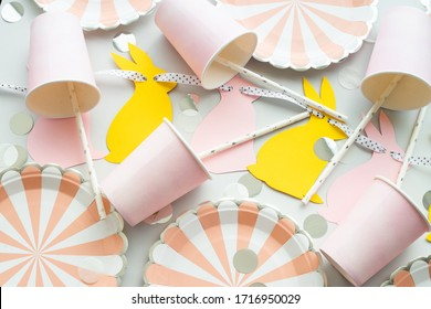 Birthday or easter party background in pink and yellow color with bunny garland. Flat lay, top view