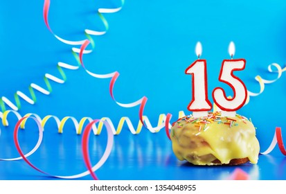 Birthday of fifteen years. Cupcake with white burning candle in the form of number 15. Vivid blue background with copy space