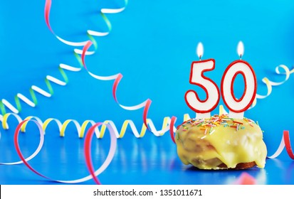 Birthday of fifty years. Cupcake with white burning candle in the form of number 50. Vivid blue background with copy space