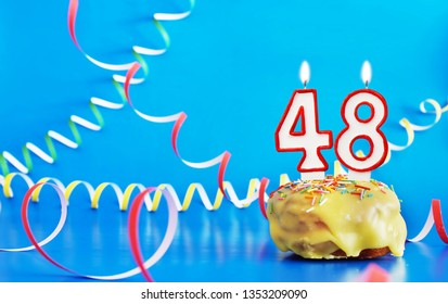 Birthday of forty eight years. Cupcake with white burning candle in the form of number 48. Vivid blue background with copy space