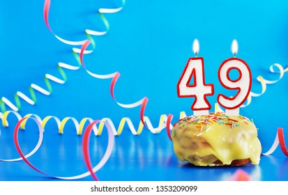 Birthday of forty nine years. Cupcake with white burning candle in the form of number 49. Vivid blue background with copy space