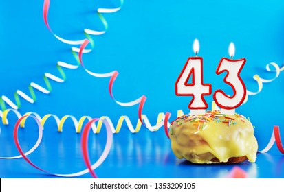 Birthday of forty three years. Cupcake with white burning candle in the form of number 43. Vivid blue background with copy space