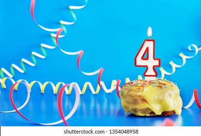 Birthday of four years. Cupcake with white burning candle in the form of number 4. Vivid blue background with copy space