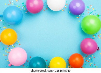 Birthday frame of colorful balloons and confetti on blue table top view. Flat lay style.