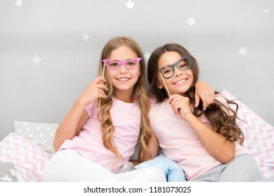 Birthday girl. Children posing with grimaces photo booth props. Pajamas party in bedroom. Friends cute and cheerful posing with eyeglasses accessories. Girls friends having fun pajamas party.