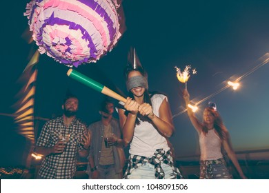 Birthday girl hitting the pinata with baseball bat while her friends are cheering and laughing. Young people having fun at a rooftop birthday party